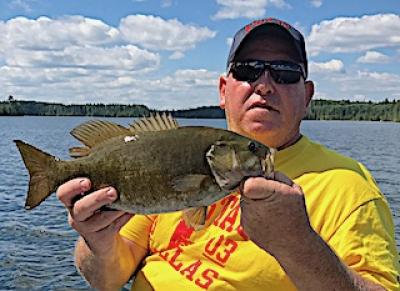 Proud Smallmouth Bass Fisher Fishing at Fireside Lodge in Canada