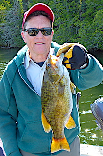 Larry With A Large Trophy Size Smallmouth Bass at Fireside Lodge in Canada