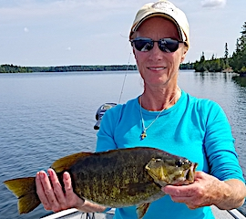 Debra Fishing Trophy Smallmouth Bass at Fireside Lodge in Canada